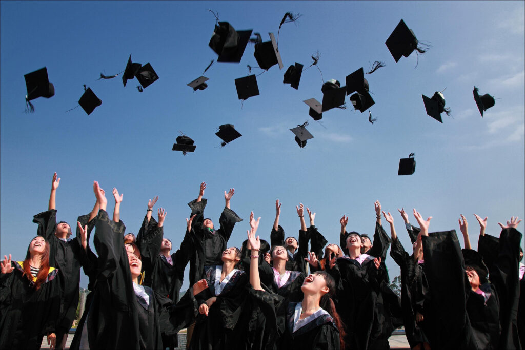 Graduates throwing up their caps into the air