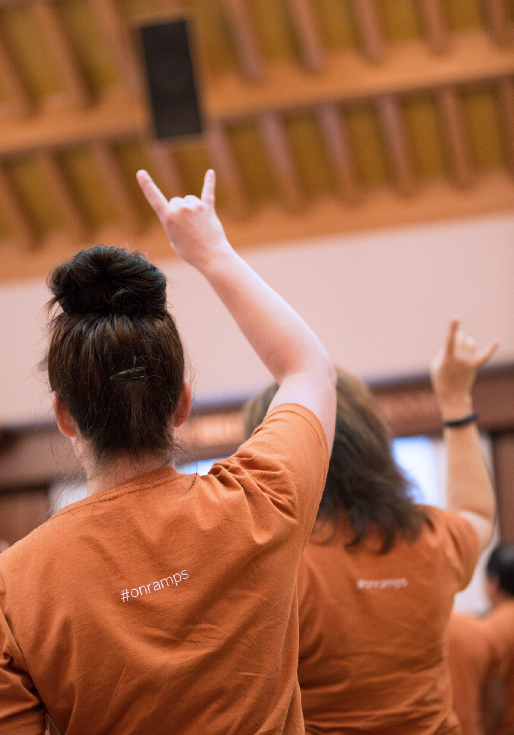 Person with OnRamps shirt on showing the UT Longhorns sign with their hand