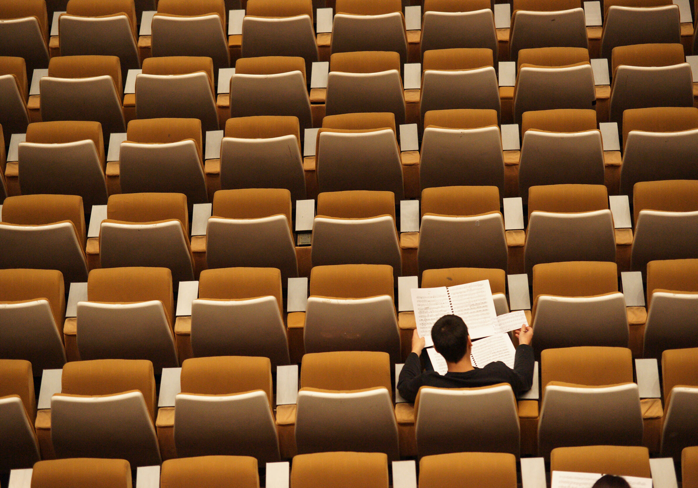 Man sitting in a row of orange chairs.